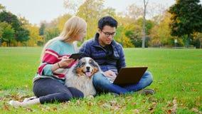 Estudiantes que se relajan en el parque El hombre asiático utiliza a una mujer del ordenador portátil con la tableta que se sient