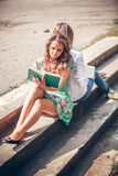 Estudiantes que se sientan con un libro en la calle Imagen de archivo libre de regalías