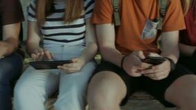 Estudiantes que se sientan en banco y que estudian con los dispositivos almacen de metraje de vídeo