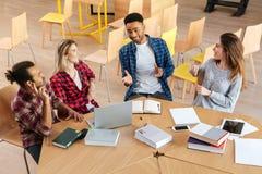 Estudiantes que se sientan en biblioteca Imágenes de archivo libres de regalías