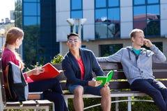 Estudiantes que se sientan en el banco Fotos de archivo libres de regalías