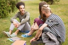 Estudiantes que se sientan en el césped que habla después de clases imagen de archivo libre de regalías