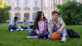 Estudiantes que se sientan en hierba cerca de la universidad, conocido, primer día en campus fotos de archivo libres de regalías