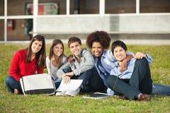 Estudiantes que se sientan en hierba en el campus de la universidad imagen de archivo libre de regalías