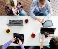 Estudiantes que se sientan en la tabla usando los ordenadores y las tabletas Foto de archivo