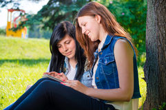 Estudiantes que se sientan en parque con PC de la tableta Imagen de archivo