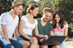 Estudiantes que se sientan en un banco con el ordenador portátil Foto de archivo libre de regalías