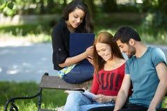 Estudiantes que se sientan en un banco y que hacen el trabajo de la escuela Fotos de archivo libres de regalías