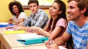 Estudiantes que se sientan en una línea que escucha en sala de clase almacen de metraje de vídeo