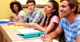 Estudiantes que se sientan en una línea que escucha en sala de clase almacen de video