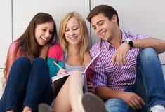 Estudiantes que se sientan junto Fotografía de archivo libre de regalías