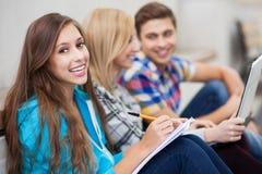 Estudiantes que se sientan junto Imagenes de archivo