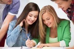 Estudiantes que señalan en el cuaderno en la escuela Imágenes de archivo libres de regalías