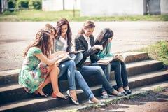 Estudiantes que sientan con los libros en la calle Fotos de archivo libres de regalías