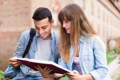 Estudiantes que sientan la lectura al aire libre un libro Foto de archivo libre de regalías
