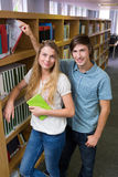 Estudiantes que sonríen en la cámara en la biblioteca Imagen de archivo