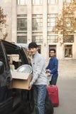 Estudiantes que sonríen y que se trasladan a dormitorio en campus de la universidad Foto de archivo libre de regalías