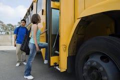 Estudiantes que suben al autobús escolar Foto de archivo