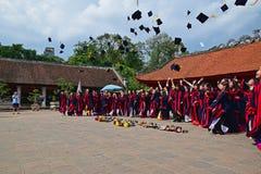 Estudiantes que tienen ceremonia de graduación en el templo de la literatura con los sombreros para arriba en el aire Imagenes de archivo