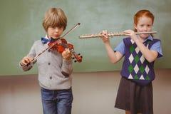 Estudiantes que tocan la flauta y el violín en sala de clase Foto de archivo