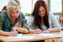 Estudiantes que toman el examen en la universidad fotografía de archivo