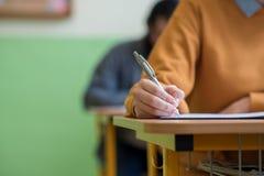 Estudiantes que toman el examen en sala de clase Prueba de la educación foto de archivo libre de regalías