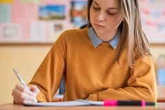 Estudiantes que toman el examen en sala de clase Prueba de la educación imagenes de archivo