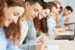 Estudiantes que toman el examen en universidad Imagen de archivo