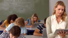 Estudiantes que toman notas y profesor que usa la PC de la tableta almacen de video