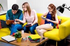 Estudiantes que trabajan en el sofá Foto de archivo libre de regalías
