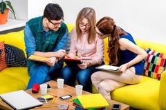 Estudiantes que trabajan en el sofá Imágenes de archivo libres de regalías