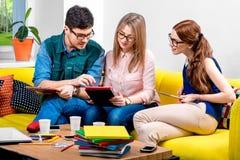 Estudiantes que trabajan en el sofá Imagen de archivo libre de regalías
