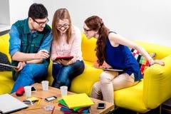 Estudiantes que trabajan en el sofá Fotos de archivo