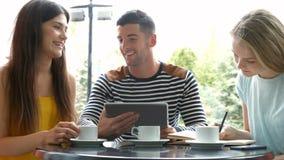 Estudiantes que trabajan en la asignación en el café del campus metrajes
