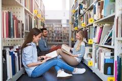 Estudiantes que trabajan en la biblioteca en el campus fotografía de archivo libre de regalías
