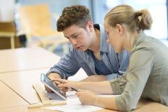 Estudiantes que trabajan en la tableta imagen de archivo