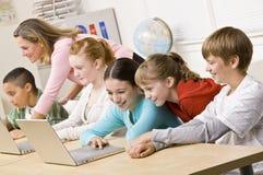 Estudiantes que trabajan en las computadoras portátiles Foto de archivo libre de regalías