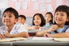 Estudiantes que trabajan en los escritorios en escuela china Fotos de archivo libres de regalías