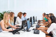 Estudiantes que trabajan en los ordenadores. foto de archivo libre de regalías