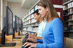 Estudiantes que trabajan en los ordenadores en biblioteca Fotos de archivo