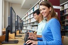 Estudiantes que trabajan en los ordenadores en biblioteca Imagenes de archivo