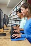 Estudiantes que trabajan en los ordenadores en biblioteca Imagen de archivo libre de regalías