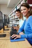 Estudiantes que trabajan en los ordenadores en biblioteca Fotografía de archivo libre de regalías