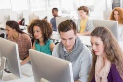 Estudiantes que trabajan en sala de ordenadores foto de archivo