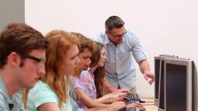 Estudiantes que trabajan en sala de ordenadores con el conferenciante metrajes