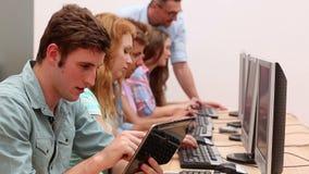 Estudiantes que trabajan en sala de ordenadores con el conferenciante almacen de metraje de vídeo