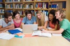 Estudiantes que trabajan junto en la biblioteca Fotos de archivo libres de regalías