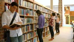 Estudiantes que trabajan junto en la biblioteca metrajes