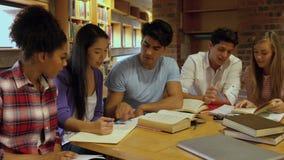 Estudiantes que trabajan junto en la biblioteca almacen de video