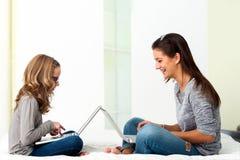 Estudiantes que trabajan junto en los ordenadores portátiles en casa Foto de archivo